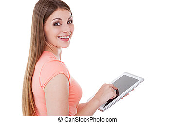 Beauty with digital tablet. Beautiful young woman using digital tablet and looking over shoulder while standing isolated on white