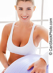 Beauty with fitness ball. Top view of attractive mature woman holding fitness ball and smiling at camera