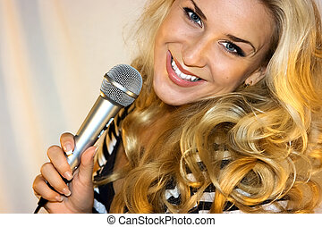 Beauty with microphone - Beautiful blond standing with...