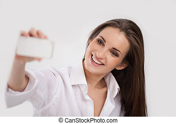 Beauty with mobile phone. Beautiful young woman photographing on her mobile phone camera and smiling while isolated on white