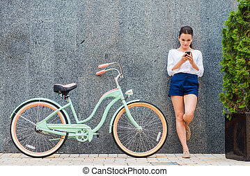 Beauty with vintage bike. Beautiful young smiling woman standing near her vintage bicycle on the street