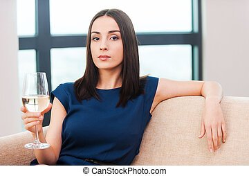 Beauty with wine. Beautiful young brown hair woman in evening gown sitting on the couch and holding glass with white wine