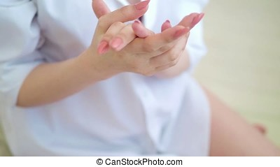 beauty woman applying cosmetic hand cream on hand on bedroom background
