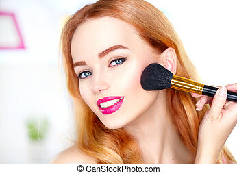 Beauty woman applying makeup. Beautiful girl looking in the mirror and applying cosmetic with a big brush