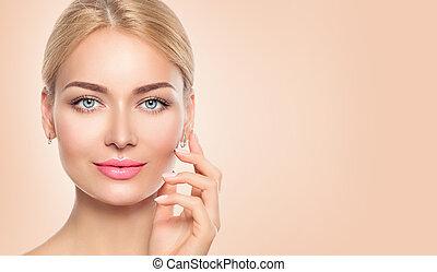 Beauty woman face closeup portrait. Spa girl touching her face
