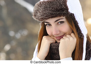 Beauty woman face portrait warmly clothed in winter holding a scarf outdoors