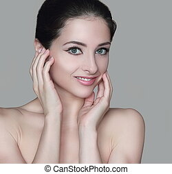 Beauty woman face with two hands at healthy skin isolated on grey background. Closeup portrait with empty space