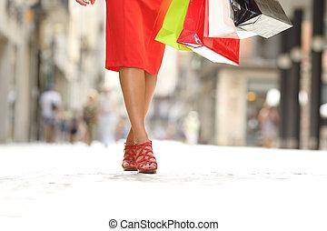 Beauty woman legs walking holding shopping bags
