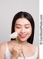 Beauty woman looking at camera with a rose flower
