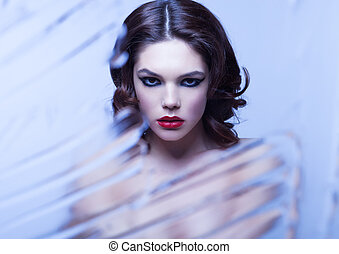 Beauty woman model with makeup through mirror