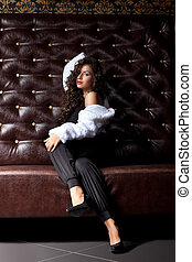 Beauty woman posing on leather sofa in dark