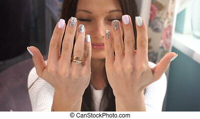 Beauty woman show her hands with manicure in spa salon....