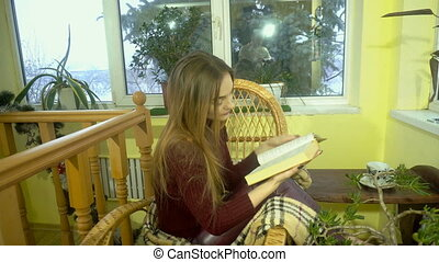 beauty woman sits in a wicker chair and reads a book with snowfall behind the window
