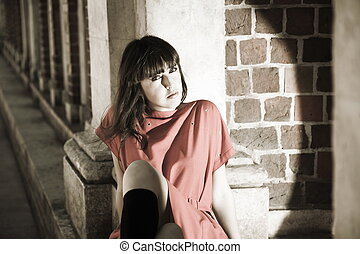 Beauty Woman Sitting Against Brick Border