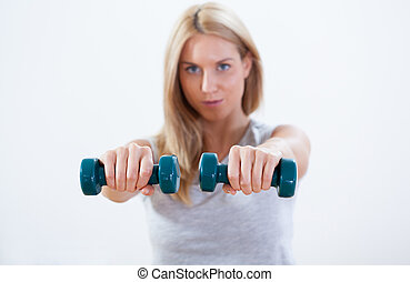 Beauty woman training with dumbbells
