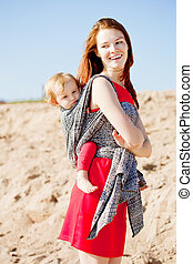 Beauty woman with a baby in a sling. Mom and baby. Mother...