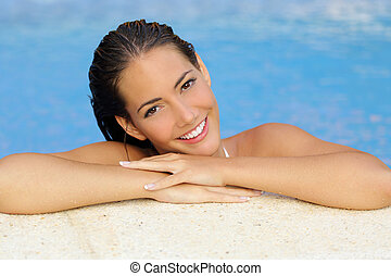 Beauty woman with perfect skin and white teeth in a pool side looking at camera