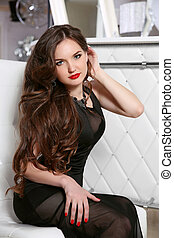 Beauty woman with red lips, long wavy hair style. Brunette girl in elegant black dress looking at camera at home.