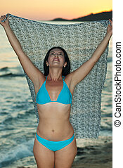 Beauty woman with scarf on beach by sunset