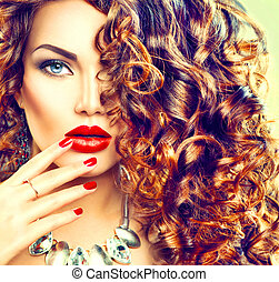 Beauty young brunette woman with curly hair, perfect makeup and manicure