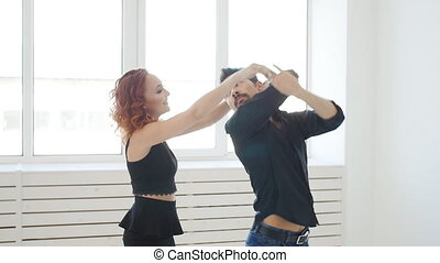 Beauty young couple dancing social dance in a white room. Kizomba or bachata or semba or taraxia