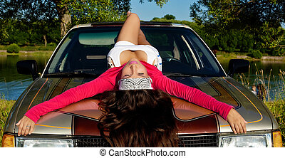 Beauty young girl lay on car at summer sunset