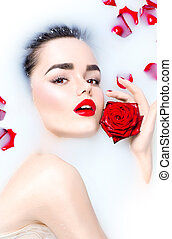 Beauty young model girl with bright makeup and red rose flower relaxing in milk bath