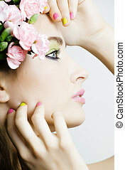 Beauty young real woman with flowers and make up closeup