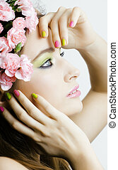Beauty young real woman with pink flowers and make up closeup, spa