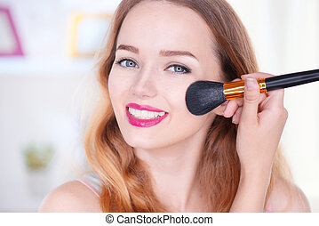 Beauty young woman applying makeup