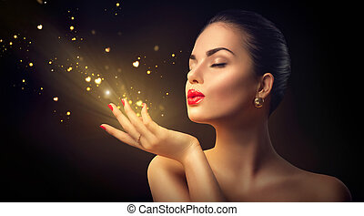 Beauty young woman blowing magic dust with golden hearts