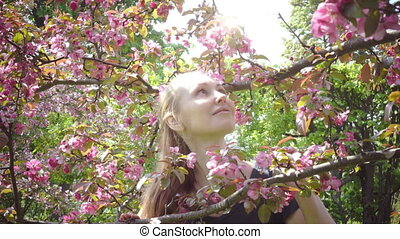 Beauty young woman enjoying nature in spring apple orchard, Happy Beautiful girl in Garden with blooming apple trees. Smiling Person smelling blossom flowers