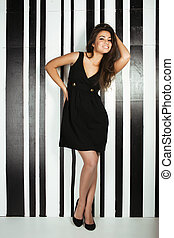 beauty young woman in black dress smiling posing