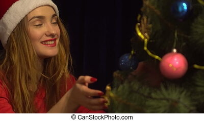 beauty young woman in santa hat smiling and dacorates a christmas tree