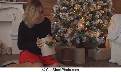 Beauty young woman opening Christmas gift box.