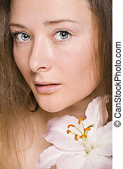 Beauty young woman with flowers and make up closeup