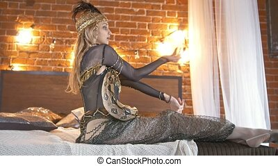 Beautyful circus actress dancing with a snake on the bed,...