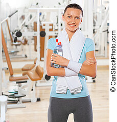 beautyful smiling standing sportswoman with bottle of water in gym