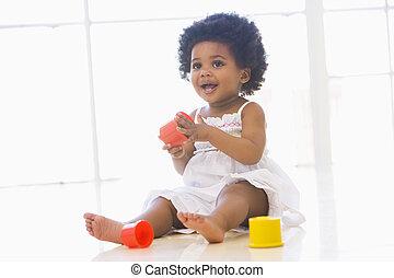 bebé, dentro, juego, con, taza, juguetes