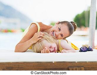bebé, feliz, madre que juega, poolside