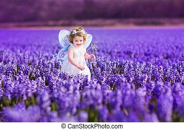bebé, niña, en, traje de hada, juego, en, un, flor, campo