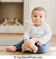 bebê sorridente, menino sentando, com, urso teddy, brinquedo, chão