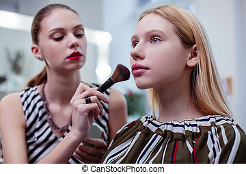 Nice attractive woman having her makeup done