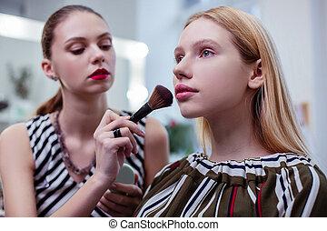 Nice attractive woman having her makeup done
