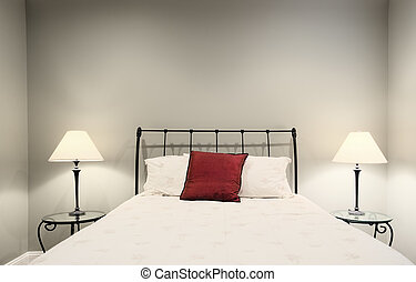 Cropped view of a white bedroom, showing a bed and two lamps on side tables. Horizontal format.
