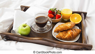 Bed breakfast with croissants,fruits, coffee and juice