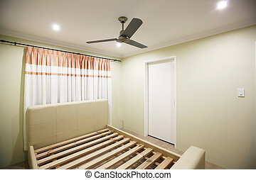 Bed frame in an empty room with beige colored wall.
