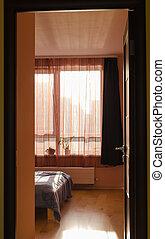 bed illuminated by sunlight window curtains