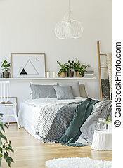 Bed in bright bedroom interior