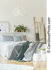 Bed in white bedroom interior